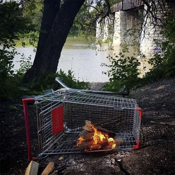 An overturned shopping cart with a bonfire inside of it