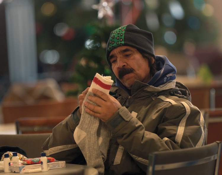 Allan Land, 55, looks at new socks he received at the Siloam Mission Christmas lunch.  (Joe Bryksa / Winnipeg Free Press)