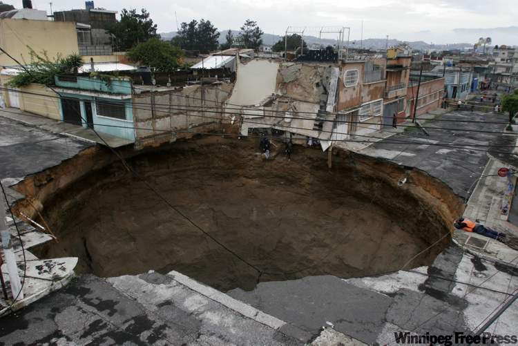 A sinkhole covers a street intersection in downtown Guatemala City, Monday May 31, 2010.
