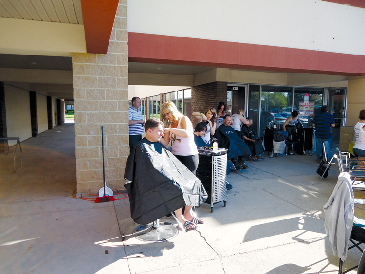 Crystal Kardynal (centre) puts the fine touches on a man's do at the haircut fundraiser last year.