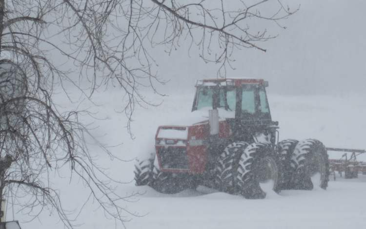 Snow rests heavy on a tractor in Alonsa, Man., Tuesday afternoon. (David Mozdzen / Submitted Photo)