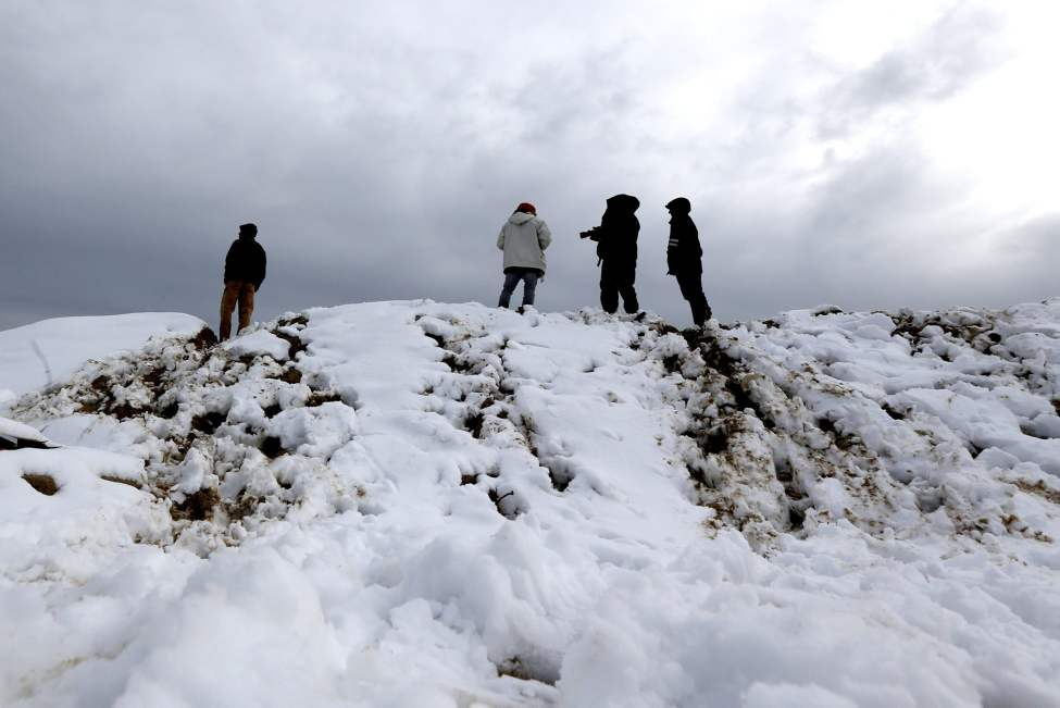 People stand on a dune covered in snow Thursday Nov. 8, 2012 in Point Pleasant, N.J., following a nor'easter on the New Jersey shore. The dune was created in preparation for the nor'easter to protect the already damaged town. (AP Photo/Julio Cortez)