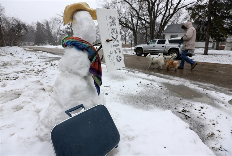 """Even with the fresh layer of snow to add to his body, this snowman on Egerton Road is eager to get out of town with a sign that reads, """"Mexico or bust."""""""