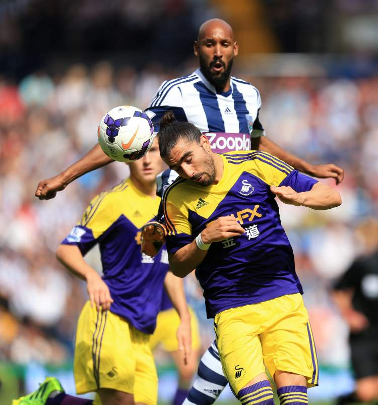 West Bromwich Albion's Nicolas Anelka (back) watches Swansea's Chico Flores, head the ball during their English Premier League soccer match in West Bromwich,  Sunday. Swansea won the game 2-0. (Mike Egerton / The Associated Press)