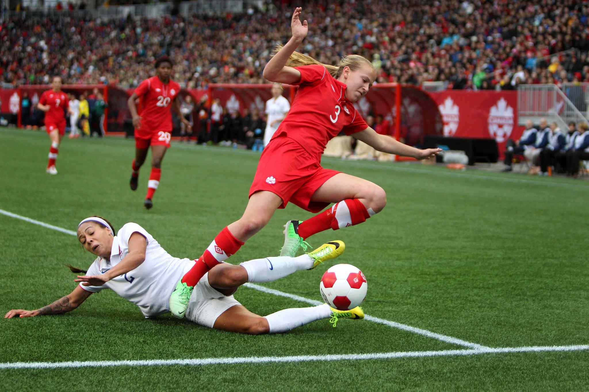 Canada's Rebecca Quinn (#3) and USA's Sydney Leroux (#2) collide while scrambling for the ball during the first half of Thursday's game at Investors Group Field.