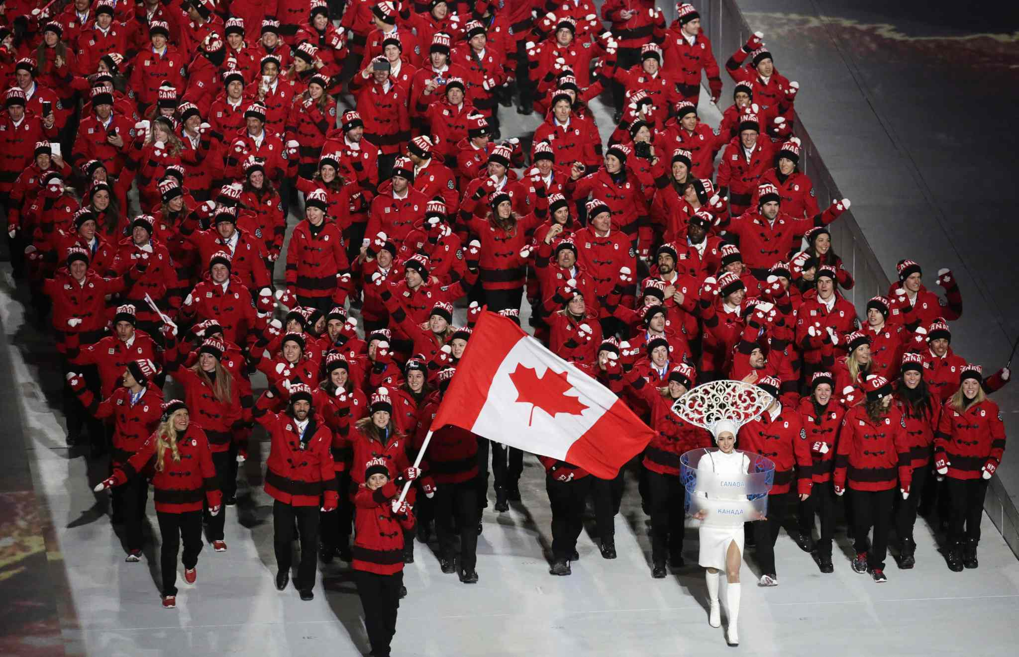 Hayley Wickenheiser of Canada carries the national flag as she leads the team during the opening ceremony of the 2014 Winter Olympics in Sochi, Russia, Friday, Feb. 7, 2014. (AP Photo/Robert F. Bukaty)