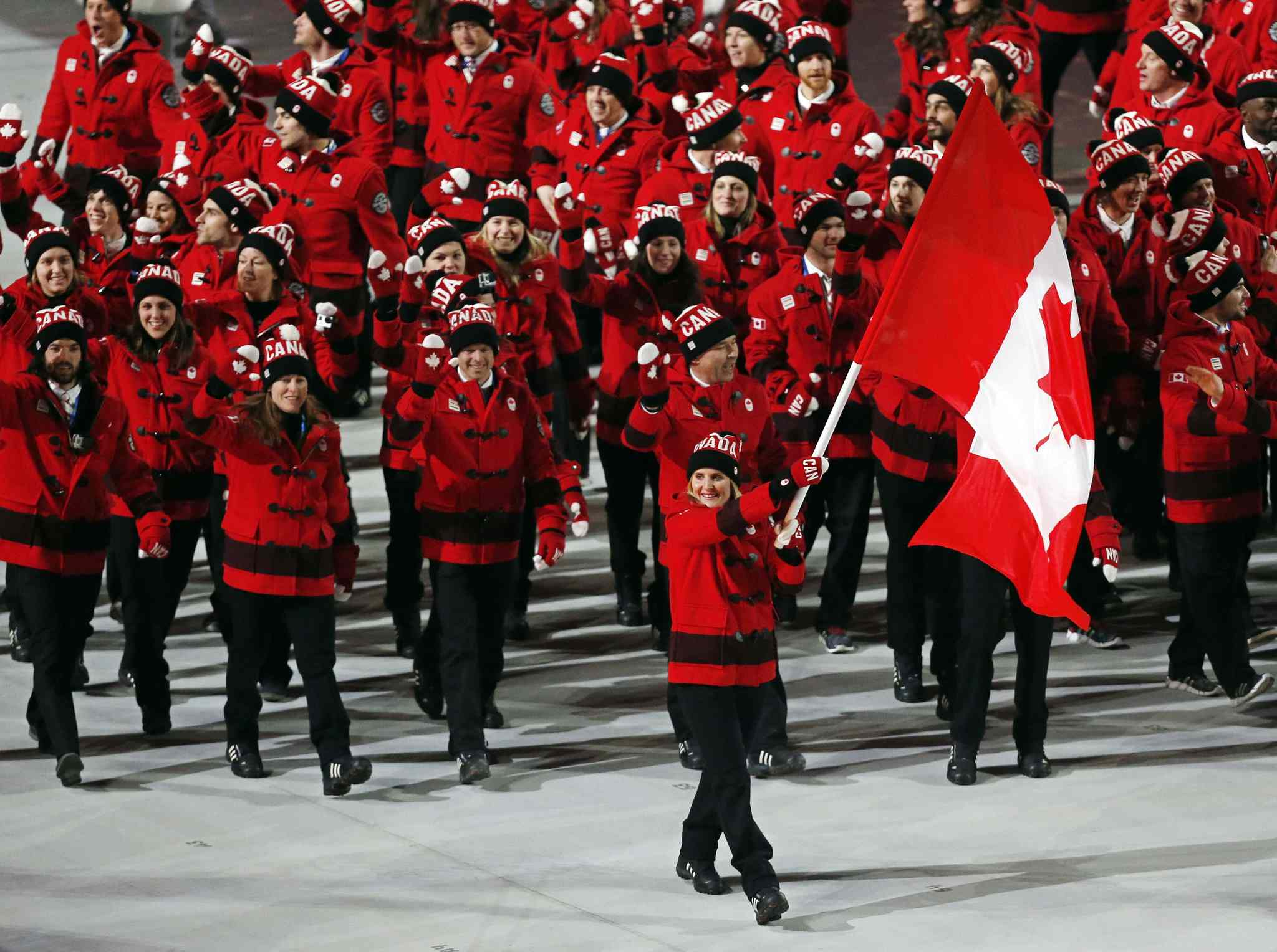 Hayley Wickenheiser of Canada carries her country flag as they arrive during the opening ceremony of the 2014 Winter Olympics in Sochi, Russia, Friday, Feb. 7, 2014. (AP Photo/Petr David Josek)