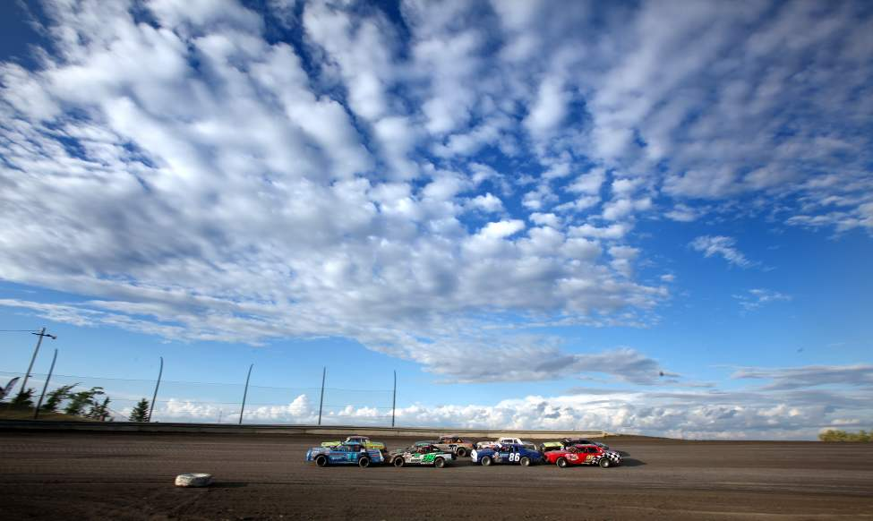 "Drivers in formation move their ""Modifieds"" toward the green flag to start an evening of racing under a prairie sky."