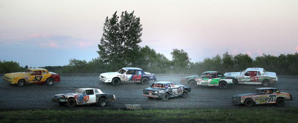 Racers round the corner on the slick dirt track race.