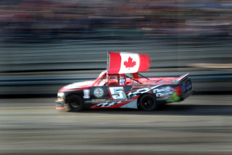 Glenn Manning parades the Canadian flag during the national anthem before opening race.
