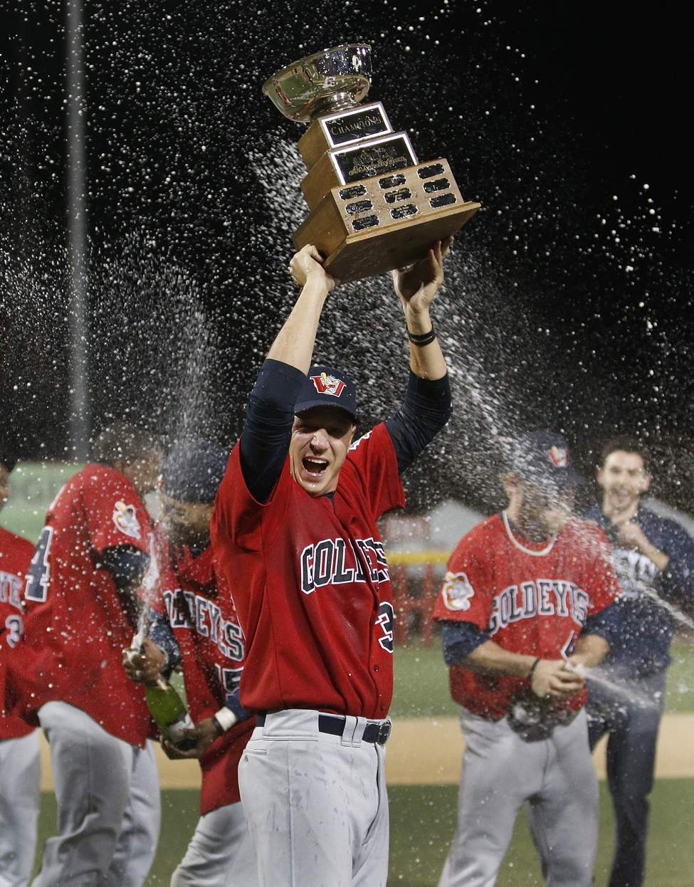 Winnipeg Goldeyes' Ace Walker holds up the trophy as the champagne flows after they defeated the Wichita Wingnuts 8-3 to win the American Association Championship in Wichita, Kansas Friday night. September 14, 2012 (Fernando Salazar / Wichita Eagle for the Winnipeg Free Press)