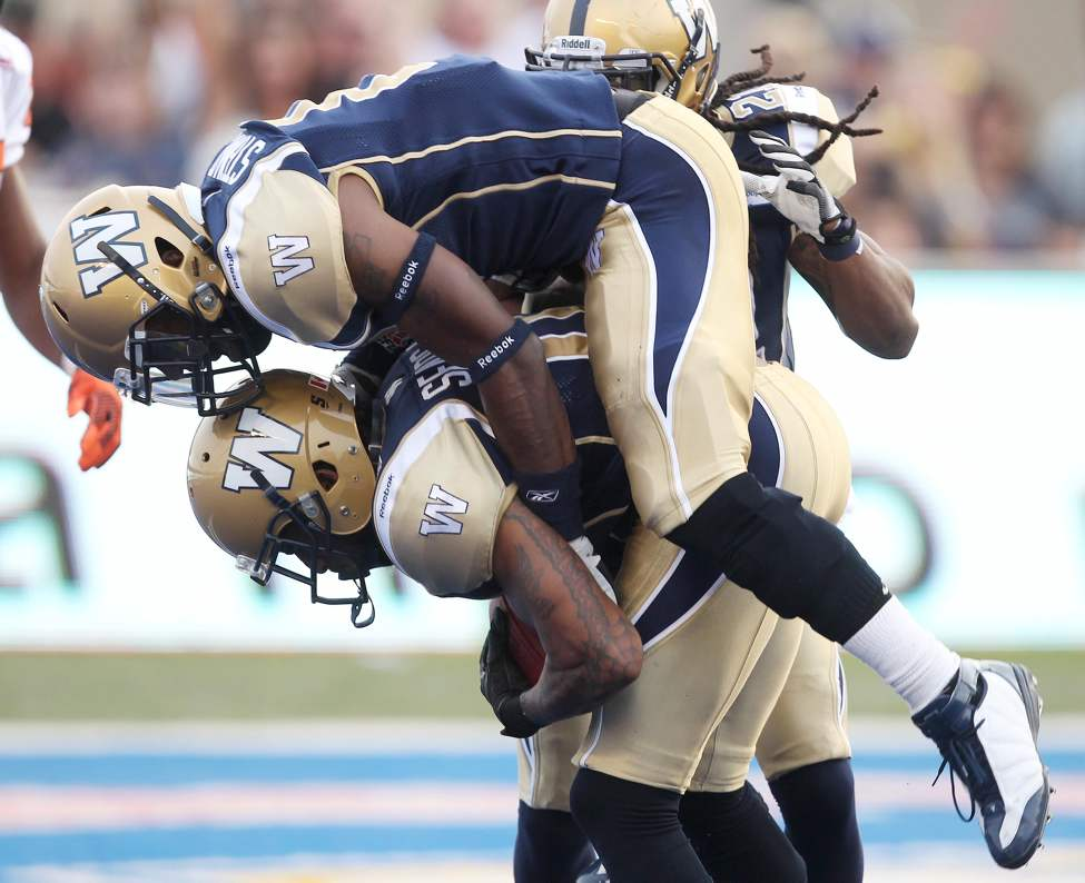 Winnipeg Blue Bombers Johnny Sears Jr, bottom, is congratulated by teammate Brandon Stewart after he intercepted a BC Lions end zone pass during first-quarter CFL action at Canad Inns Stadium Friday night. August 24, 2012   (JOE BRYKSA / WINNIPEG FREE PRESS)