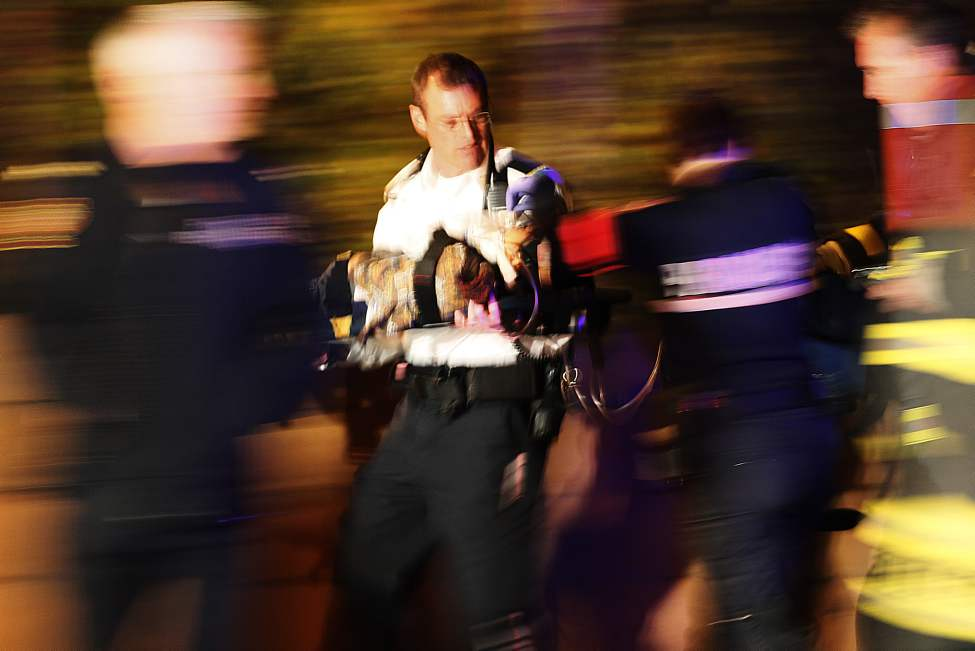 A paramedic rushed a child to a waiting ambulance. Police and emergency personnel attend to a two vehicle collision in Winnipeg Tuesday, October 23, 2012. Several people including children were taken to hospital. A seven-year-old child later died in hospital. (John Woods / Winnipeg Free Press)