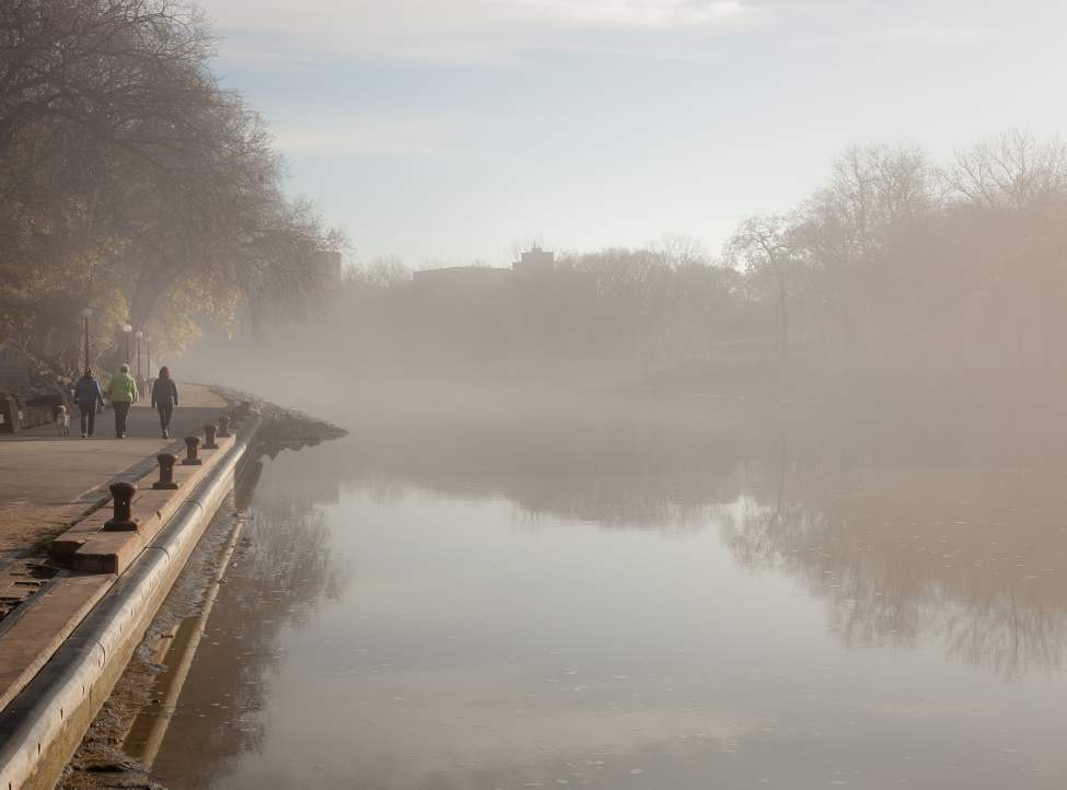 The Assiniboine River was blanketed in fog this morning. Walkers along the River Walk near the Legislative Building enjoy a misty stroll. (Melissa Tait / Winnipeg Free Press)
