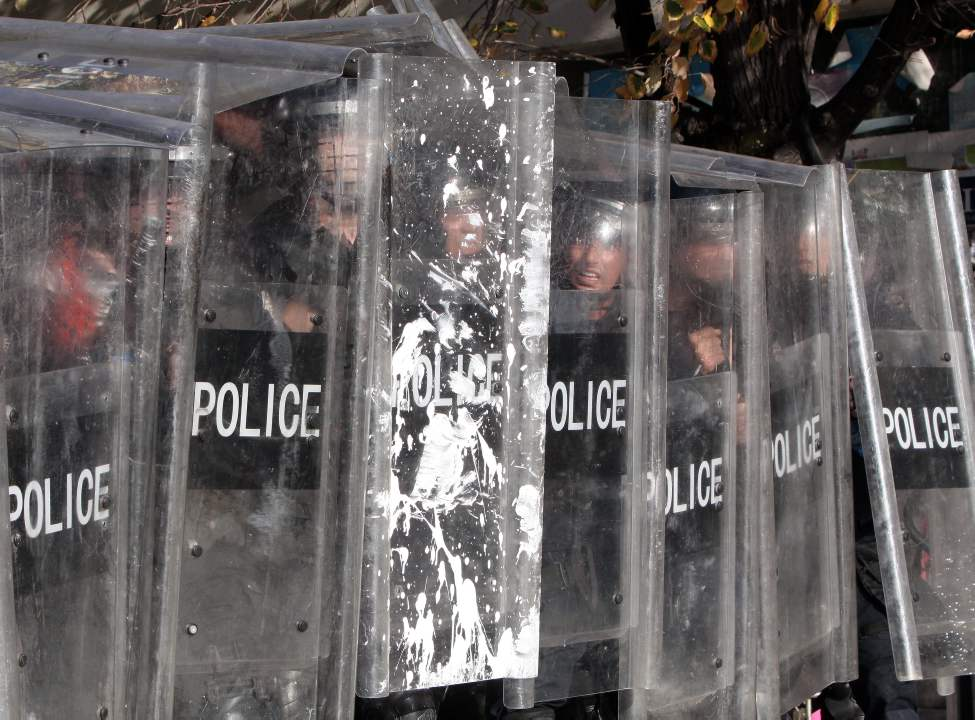 "Kosovo police officers take cover behind shields as supporters of the opposition party ""Self Determination"" throw stones during a protest in Kosovo capital Pristina on Monday, Oct. 22, 2012. Kosovo police in riot gear fired tear gas and used batons to disperse dozens of ethnic Albanians protesting a meeting between Prime Minister Hashim Thaci and Serbian leader Ivica Dacic. Protest early Monday was called by Self-Determination, a hardline opposition group that opposes any talks with Serbia. (AP Photo/Visar Kryeziu)"