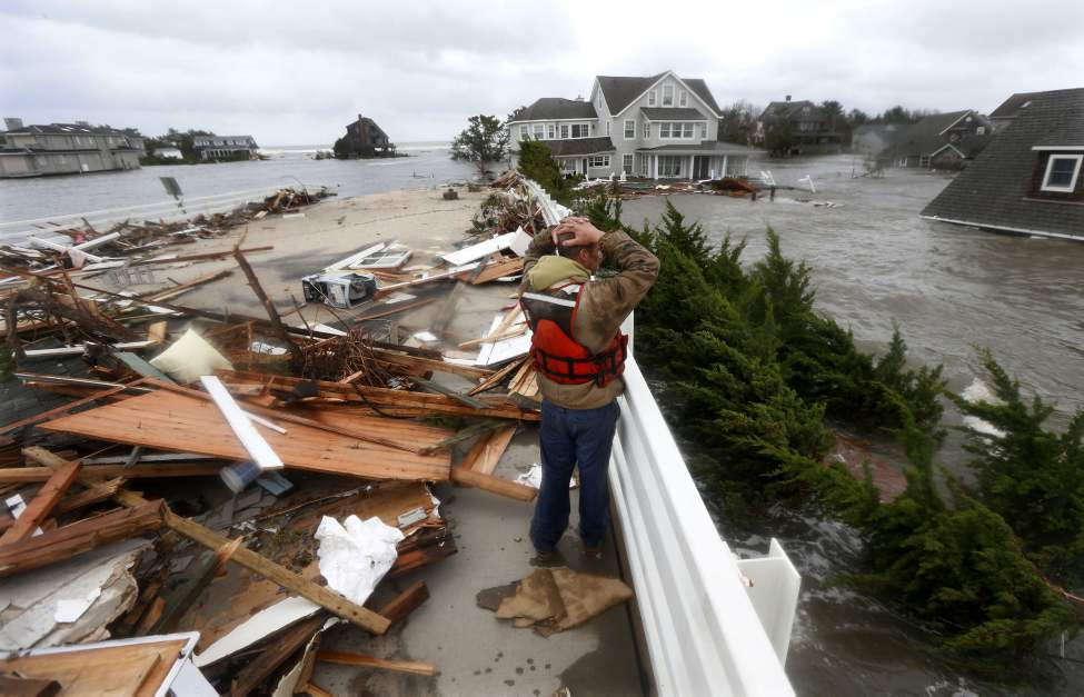 Brian Hajeski, 41, of Brick, N.J., reacts as he looks at debris of a home that washed up on to the Mantoloking Bridge the morning after superstorm Sandy rolled through, Tuesday, Oct. 30, 2012, in Mantoloking, N.J. Sandy, the storm that made landfall Monday, caused multiple fatalities, halted mass transit and cut power to more than 6 million homes and businesses. (AP Photo/Julio Cortez)