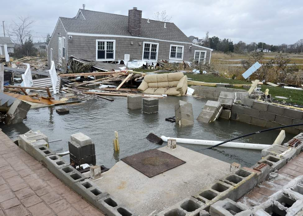 This Tuesday, Oct. 30, 2012 photo shows a house, background, pushed off its foundation, foreground, by superstorm Sandy in East Haven, Conn. (AP Photo/Jessica Hill)