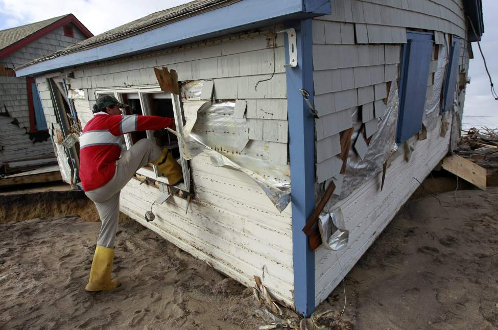 Christopher Hannafin, of South Kingstown, R.I., enters a friend's cottage through a window to salvage belongings from the structure destroyed by Superstorm Sandy, on Roy Carpenter's Beach, in the village of Matunuck, in South Kingstown, Tuesday, Oct. 30, 2012. Sandy, the storm that made landfall Monday, caused multiple fatalities, halted mass transit and cut power to more than 6 million homes and businesses. (AP Photo/Steven Senne)
