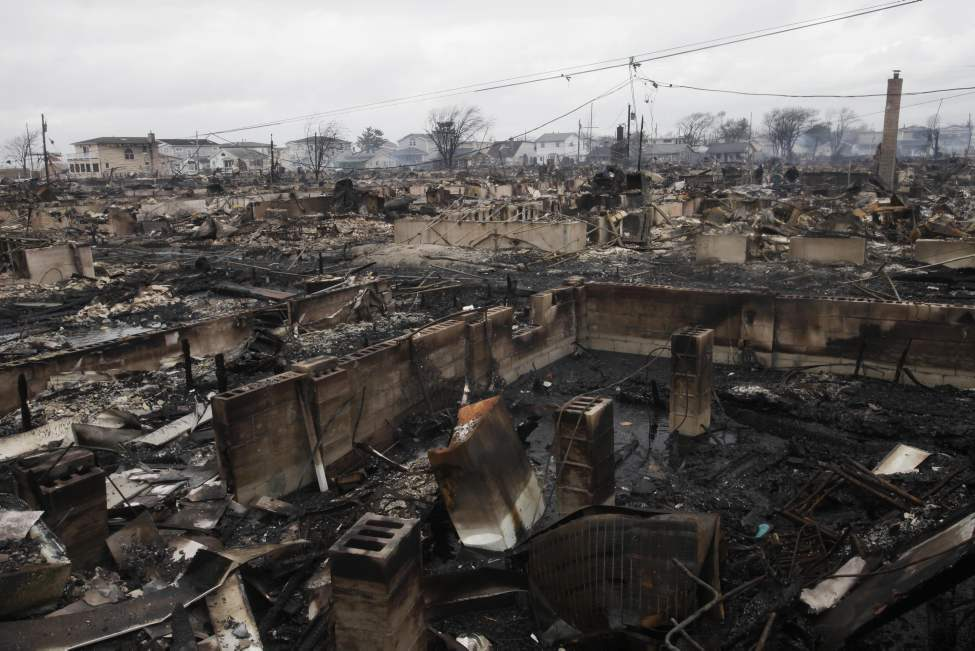 Cinderblock foundations stand amidst the smoldering ruins of a house in the Breezy Point section of New York, Tuesday, Oct. 30, 2012. More than 50 homes were destroyed in a fire which swept through the oceanfront community during superstorm Sandy. (AP Photo/Mark Lennihan)