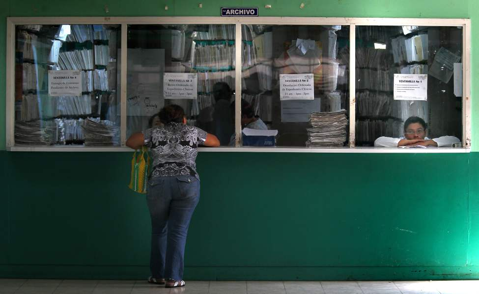 "A patient waits ""patiently"" for documents at Managua's Hospital Escuelda, Dr. Roberto Caulderon Gutierrez records window. (Phil Hossack / Winnipeg Free Press)"