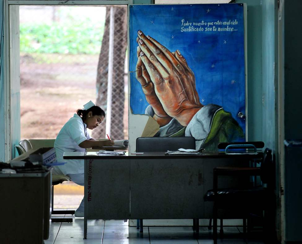 "Wearing a traditional nurses ""cap"" a nicaraguan nurse takes care of record keeping behind a prayer poster on an emergency ward in Managua. (Phil Hossack / Winnipeg Free Press)"