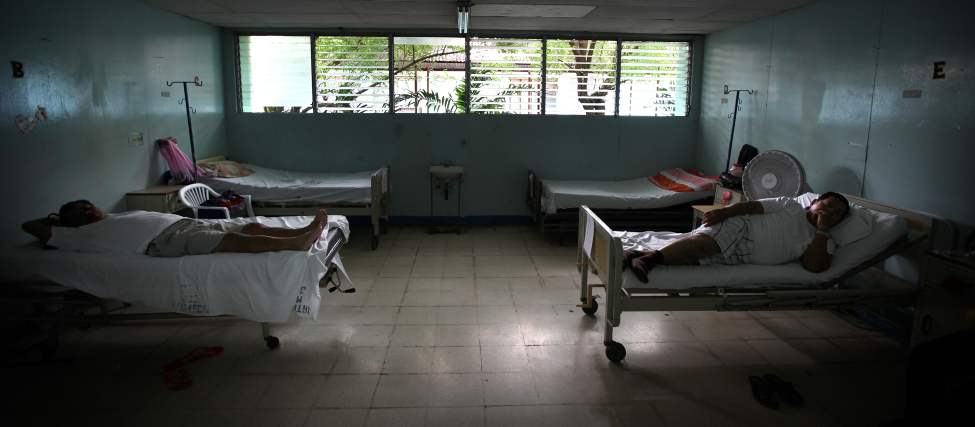 Patients wait on their beds for surgery in the men's ward.