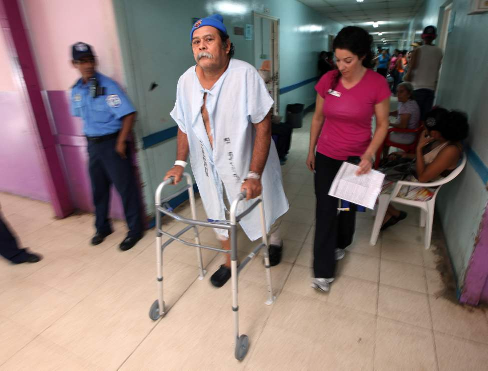 Juan Canda explores the hallway near his recovery ward under the watchful care of staff.