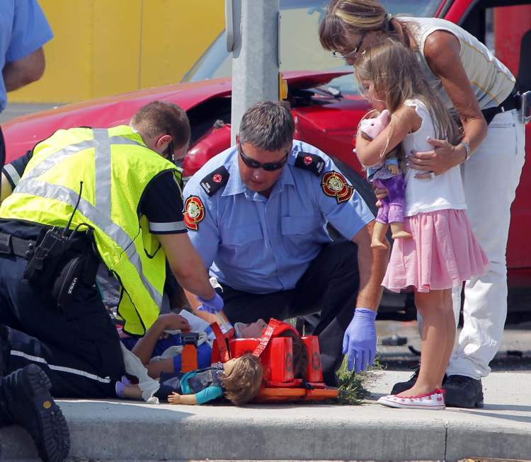 This photograph captures the peak emotional moment of an accident on McGillivray Blvd. July 13. With dolls nearby, an unidentified woman comforts one young girl while another is tended to by paramedics. I hope photos such as this move people to take better care while on the roads.  (Boris Minkevich/Winnipeg Free Press)