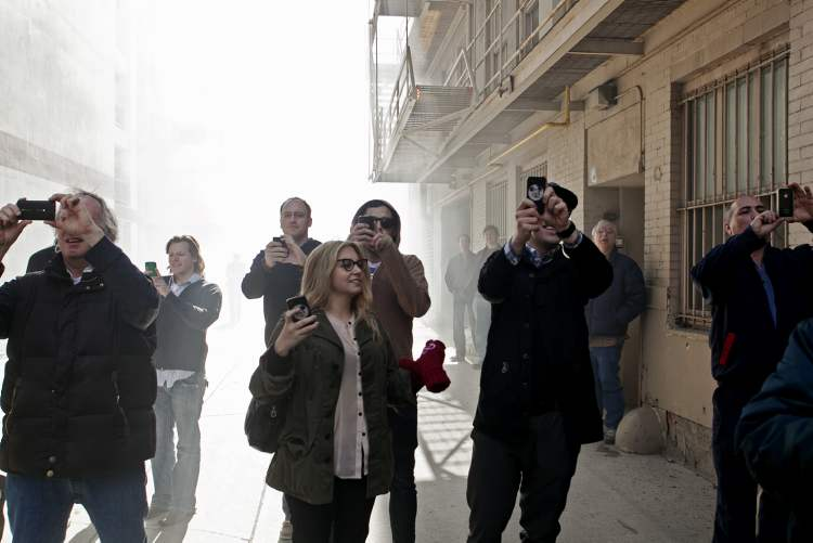 The photographer, keen to her surroundings, turned away from a fire on Albert Street on April 19 to get this beautiful commentary on social media and technology's role in the brave new world of journalism.  (Melissa Tait / Winnipeg Free Press)