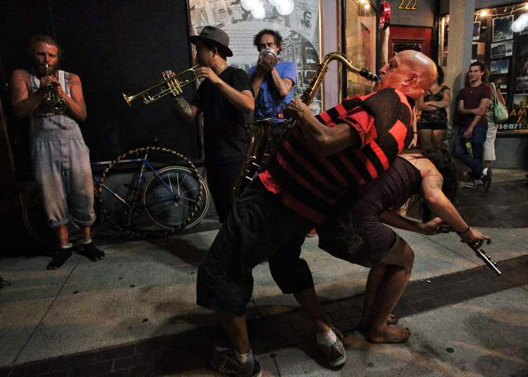 The Flaming Trolleys practise outside Ragpickers on McDermot Avenue July 25. I love the vibe of this photo - so full of life! The bare, dirty feet of the flute player clinched it as one of my favourites.  (Mike Deal / Winnipeg Free Press)