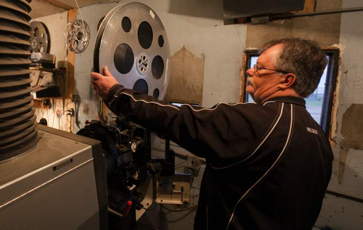 Terry Nelson adjusts the film reel on one of the projectors just before showtime at the Stardust Drive-In in Morden. (Melissa Tait / Winnipeg Free Press)