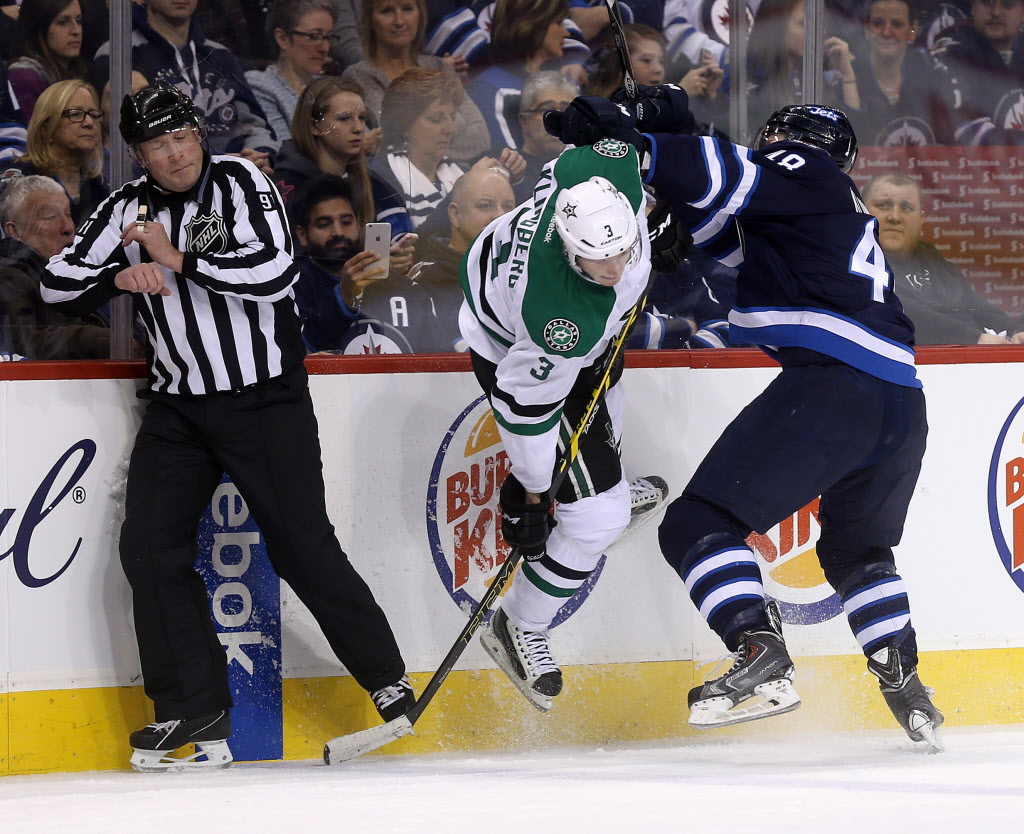 Dallas Stars' John Klingberg (3) is hit hard into the boards by his brother, Winnipeg Jets' Carl Klingberg (48) during the second period of Tuesday's game. (Trevor Hagan / The Canadian Press)