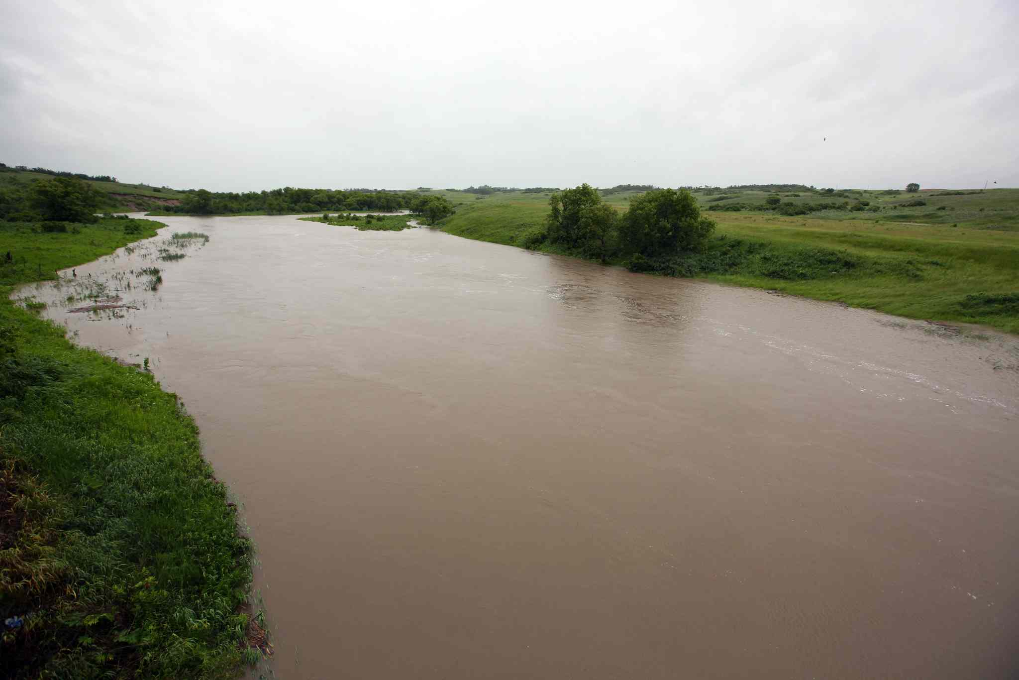 The Pipestone Creek swells over its banks west of Kola, Man. as rain falls on Sunday morning.