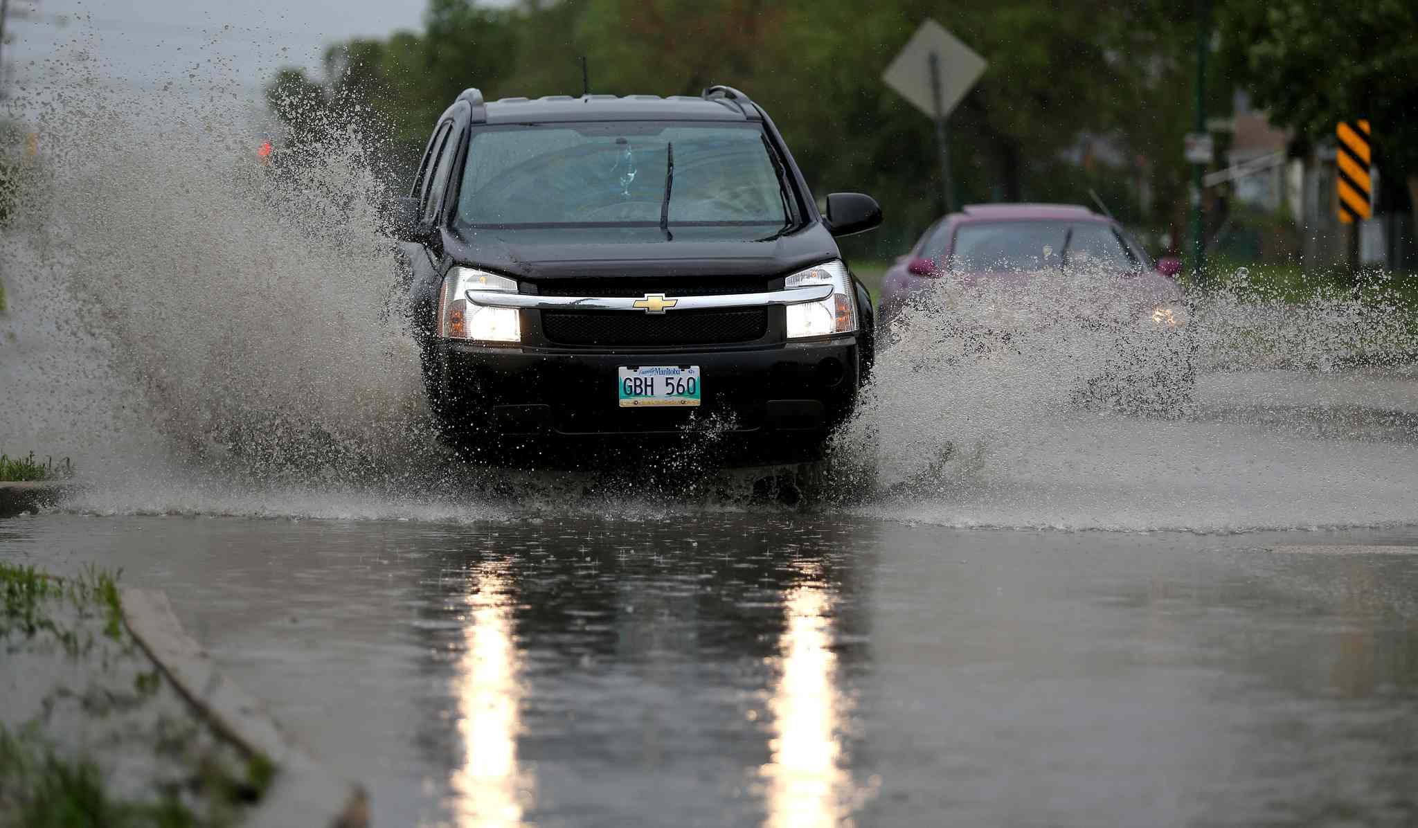 Vehicles splash through a deep puddle at Notre Dame Avenue and Border Street, Sunday, June 29, 2014.