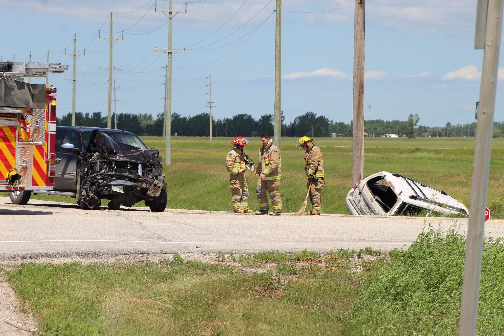 Members of the Ritchot Fire Department sweep up debris at the site of a two-vehicle collision at the intersection of Highway 59 and Provincial Road 210 south of Ile des Chenes on Monday afternoon.