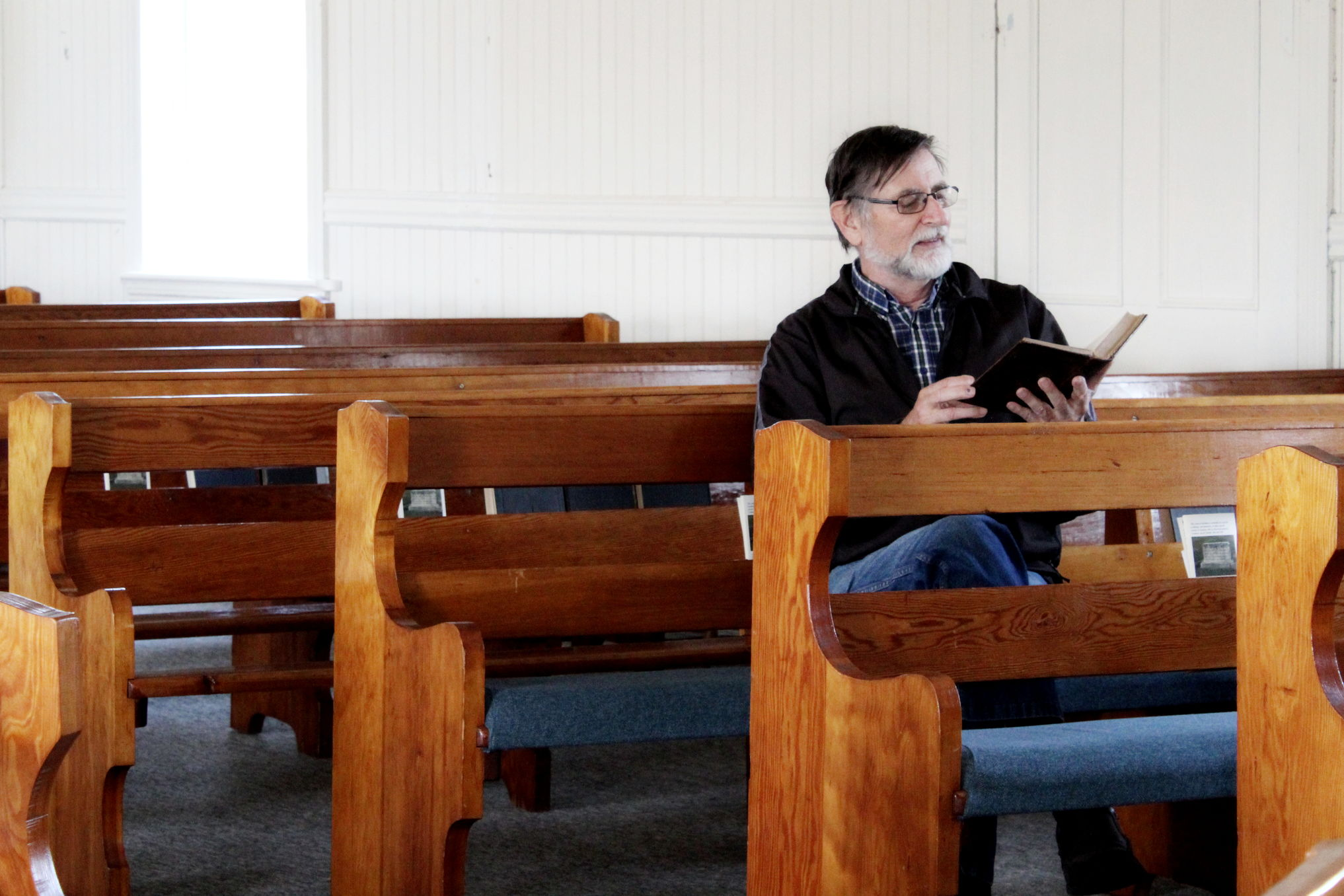 Ernest Braun flips through one of the old hymnals used by Mennonite immigrants at the Chortitz Heritage Church in Randolph.
