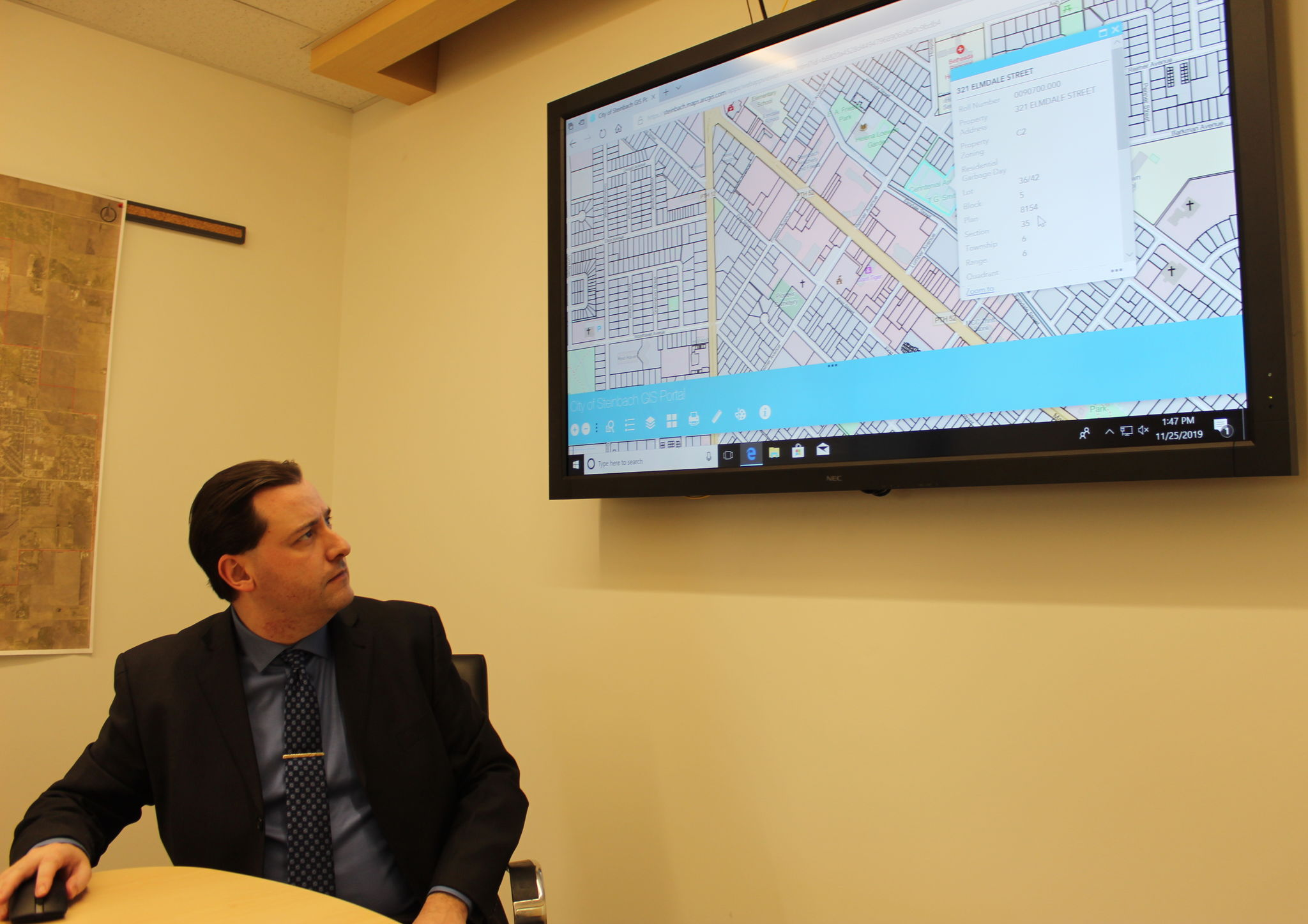 Mitchell Eastley, the City of Steinbach's GIS technician, demonstrates the mapping software on a conference room smartboard at city hall.
