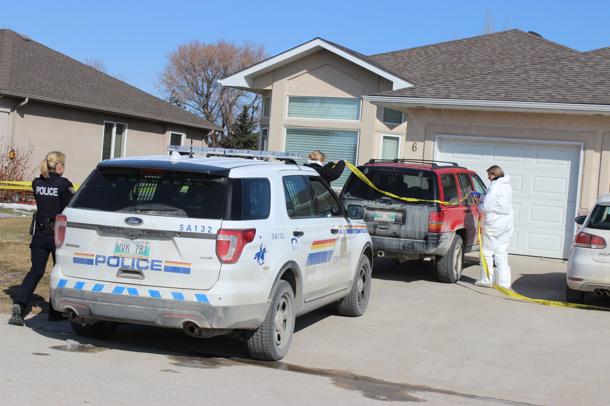 Investigators adjust police tape surrounding a home on Parkwood Cove in Steinbach on Sunday morning. RCMP said in a release that officers found a father and son dead in the home on Saturday. The deaths are considered suspicious but police added that no other individuals or suspects are being sought in the matter.