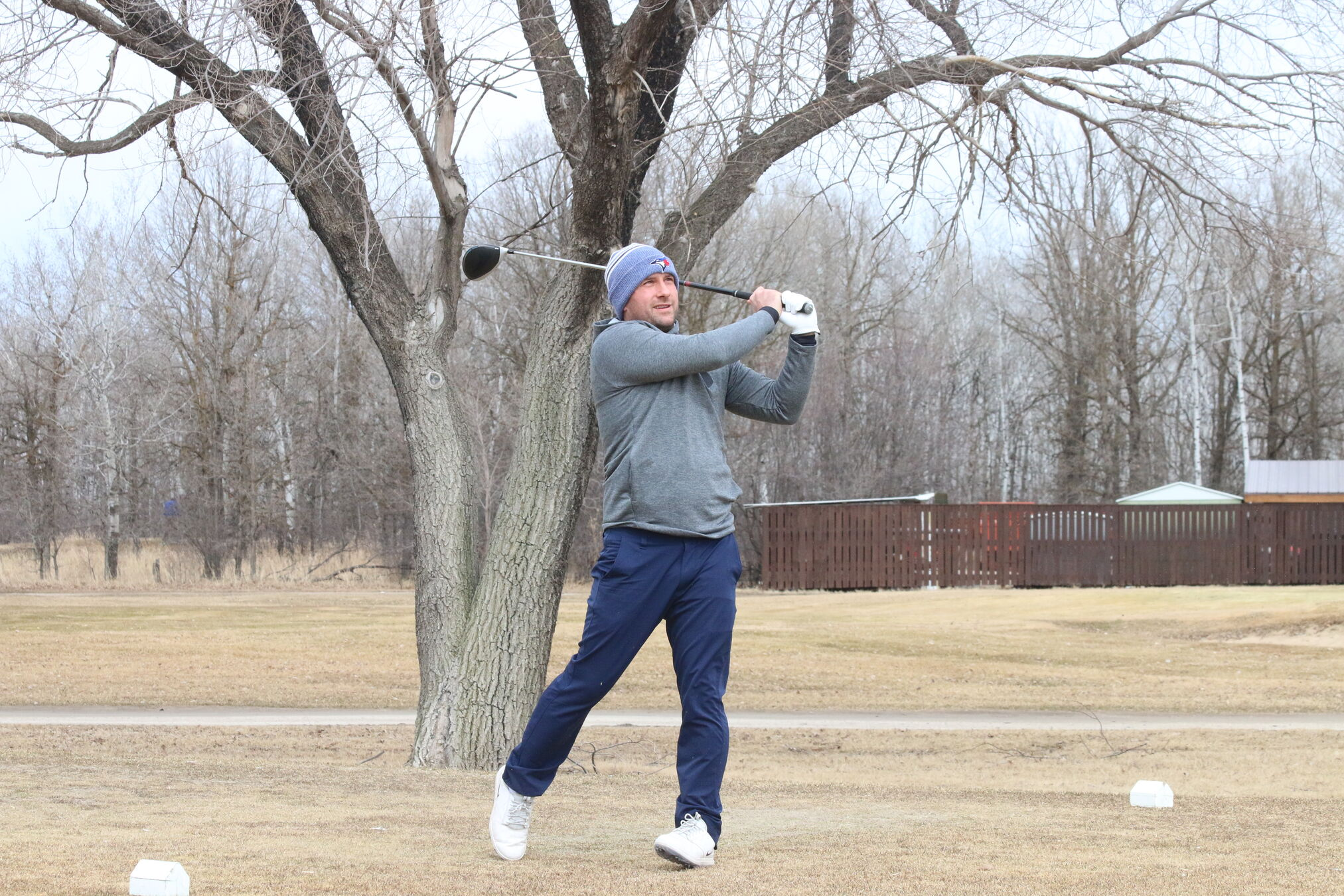With the temperature surpassing 20 degrees on Monday, Dan Patenaude tees off at a packed Oakwood Golf Course in his first round of the year.