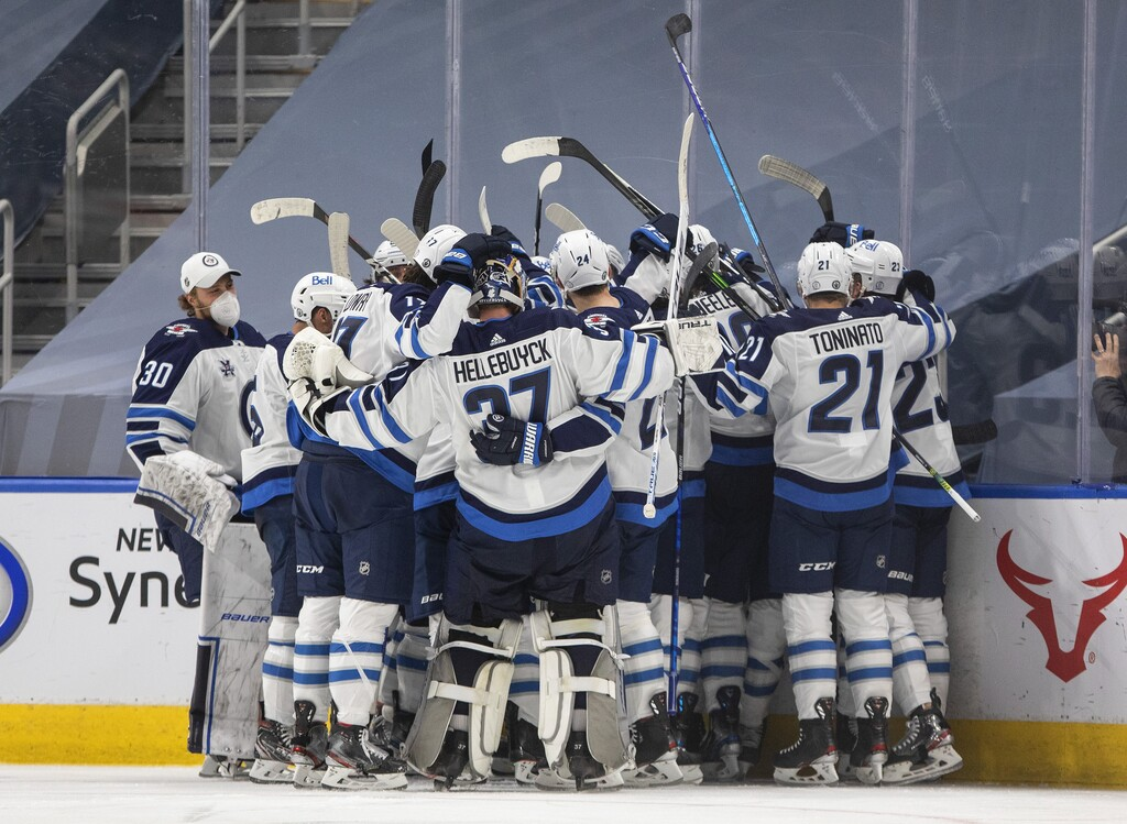 Winnipeg Jets players celebrate the win over the Edmonton Oilers after Paul Stastny scored at 4:06 in the first overtime period. (Jason Franson / The Canadian Press)