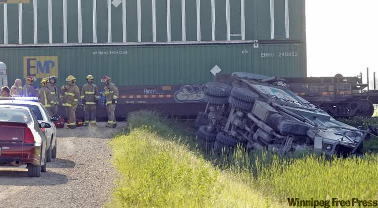 Fire crews observe scene of crash between garbage truck and train in the RM of Ritchot, near St. Adolphe.