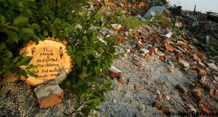 A home-made plaque, dedicated to former students of the Brandon Indian Residential School, lies tucked in the rubble of the building.