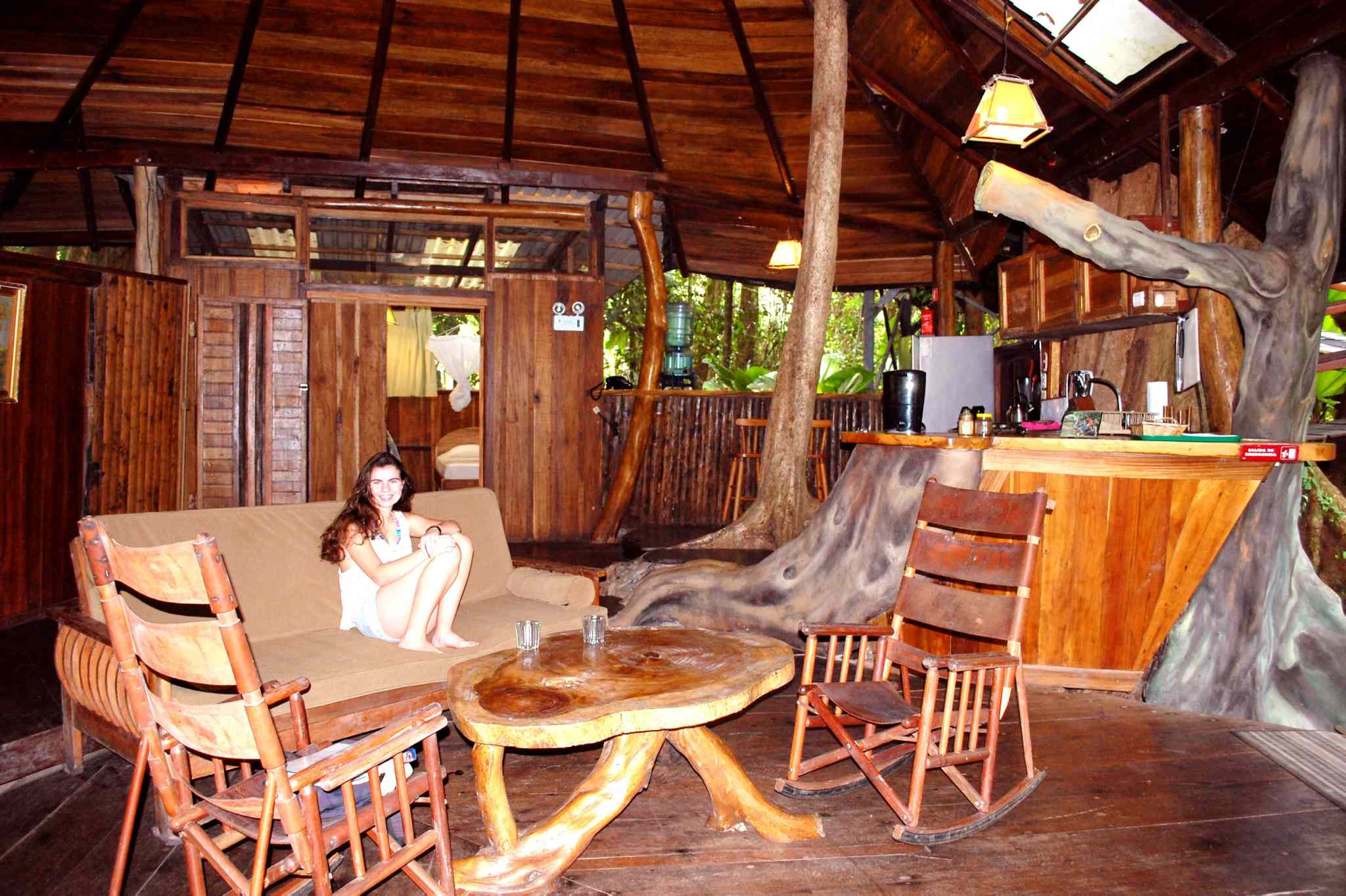 The main floor of Tree House Lodge features an open-air living room and kitchen with a live Sangrillo tree growing out of the floor and disappearing through the ceiling.