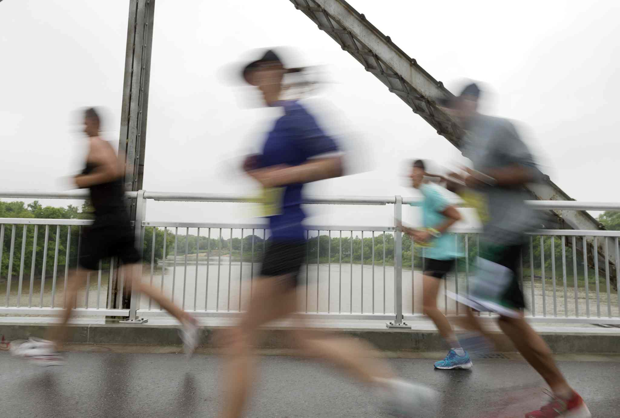 Marathon participants run over the Elm Park Bridge on Sunday morning.