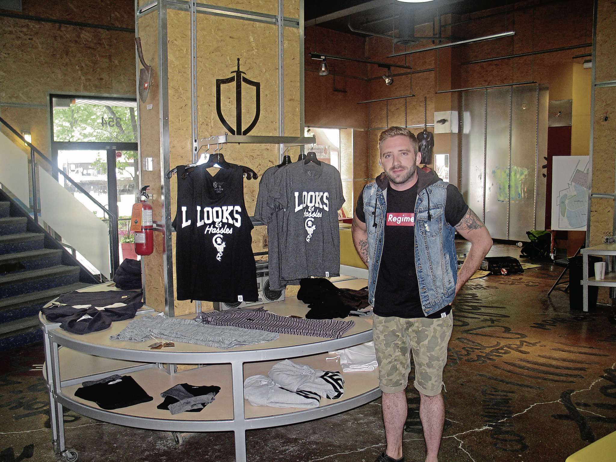 July 27, 2016 - Eric Olek poses with some of his designs at Friday Knights Clothing at 354 Portage Ave.
