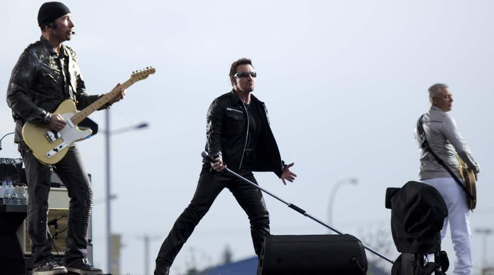 U2 guitarist The Edge, lead singer Bono, and bassist Adam Clayton perform at Canad Inns Stadium Sunday night.