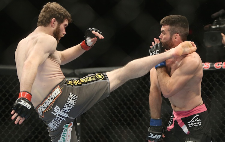 Mitch Clarke (left) hits John Maguire with a head kick during their lightweight bout at UFC 161 in Winnipeg Saturday.
