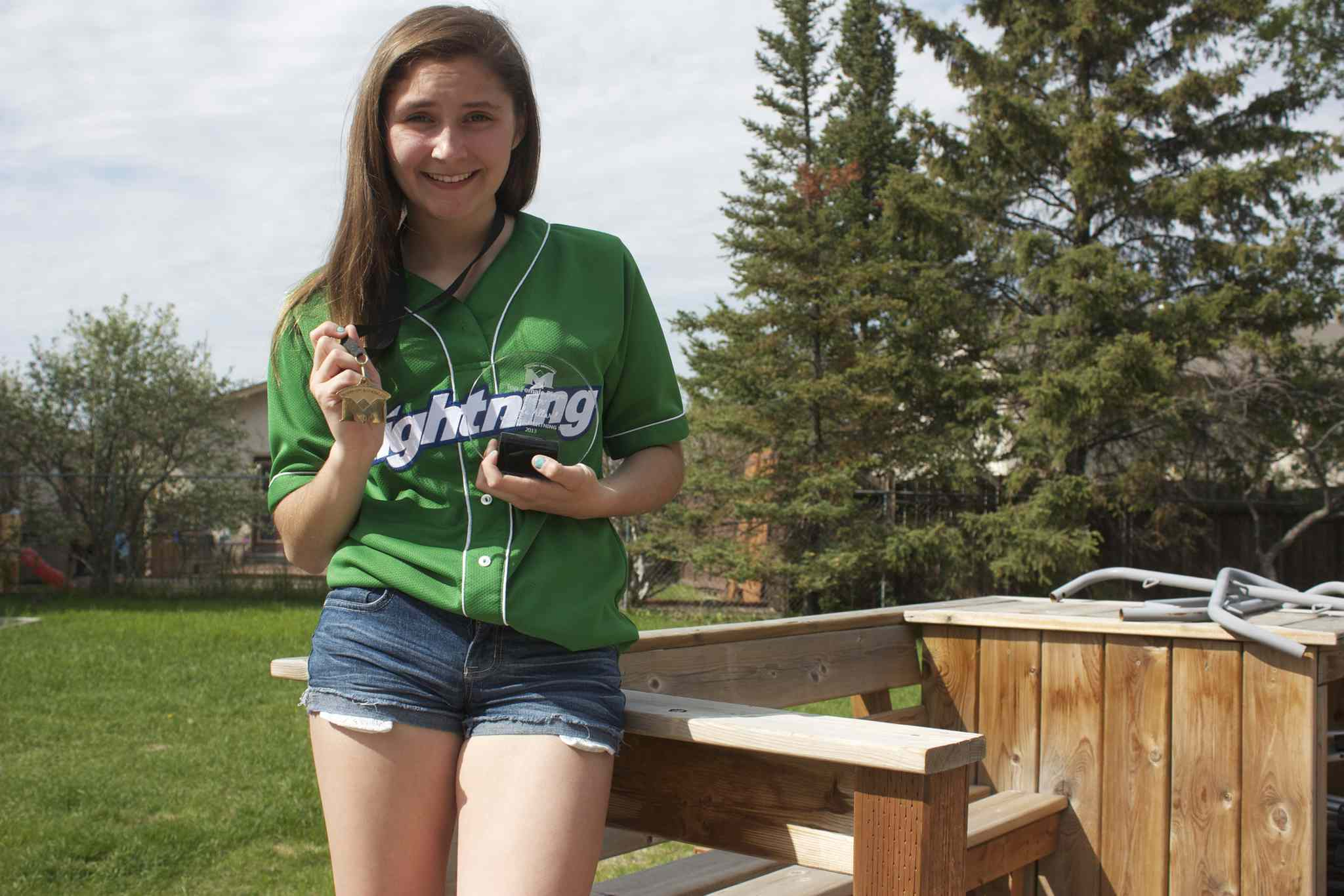 Winnipeg Lightning '99s catcher Kayla Allard shows off her provincial gold medal and MVP award from last season.