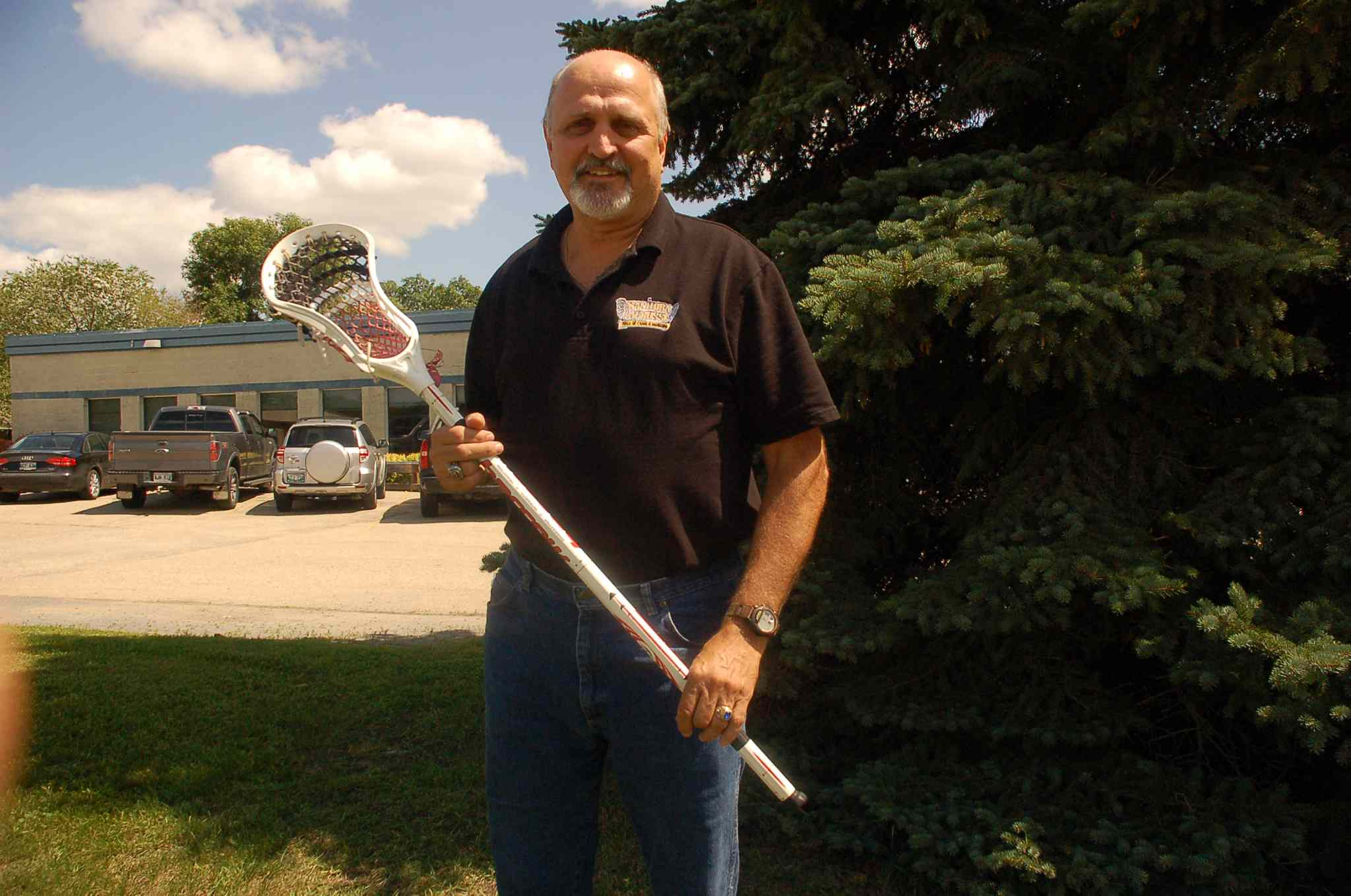 Provincial team lacrosse star Keith McLennan is shown with a lacrosse stick he is repairing. McLennan fixes sticks for free at local games, and even on his lunch break.