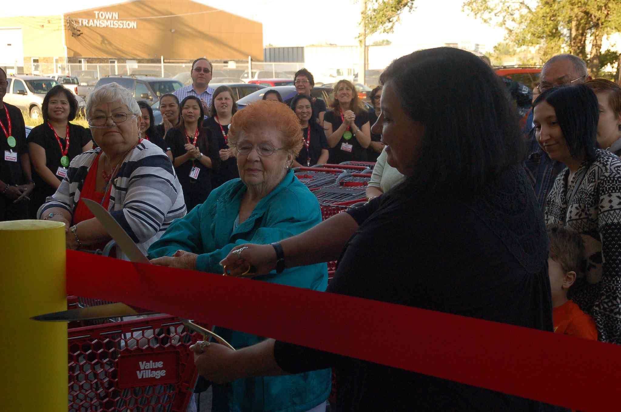 Value Village Nairn Avenue store manager Sherri Hill cuts the ribbon officially opening the relocated location on Aug. 28 as eager shoppers look on.